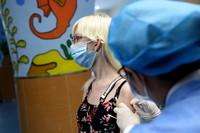 5月12日,在合肥市一处新冠疫苗接种点,医务人员为外籍人士接种疫苗。