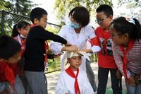 5月12日,兰州市东郊学校校医康素荣(右三)在防灾减灾安全教育活动上给学生讲解紧急包扎的要领。新华社记者 陈斌 摄