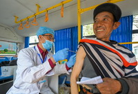 5月13日,在大榆树乡大榆树村,医务人员在流动接种车内为村民接种。