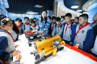5月13日,工作人员在给青岛长江学校小学部的学生讲解水下机器人的工作原理。