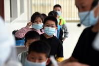5月17日,在六安市清水河学校第二小学,学生们排队等待核酸检测。