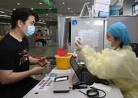 5月18日,在上海市徐汇区凯旋南路接种点,护士在注射前向市民展示腺病毒载体疫苗信息。