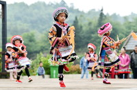 5月19日,在贵州省龙里县谷脚镇茶香村,孩子们在庆祝活动中跳芦笙舞。