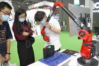 5月25日,客商在2021广州国际汽车技术展览会上参观了解关节臂三坐标测量仪。