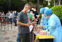 5月27日,在廣州荔灣區中海錦佳華庭小區核酸檢測點,醫務人員核對前來進行核酸檢測的市民的信息。