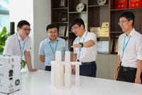 曹亞軍(右二)在科技創新工作室和團隊成員共同研究運用最新的技術方案能否在重慶來福士水晶連廊提升工程實施中實現碳中和(2021年5月28日攝)。新華社記者 劉大偉 攝