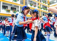 5月31日,南寧市濱湖路小學長虹校區的高年級同學為新入隊少先隊員系紅領巾。