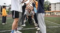 6月1日,在廣西河池市都安瑤族自治縣高級中學操場上,高三年級一位班主任帶領學生開展游戲活動。