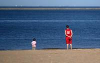 在天津市濱海新區東疆港人工沙灘,家長和小朋友一起背手望向大海(6月5日攝)。新華社記者 李然 攝