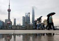6月10日,游客在雨中游覽上海外灘。