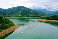 6月15日,臨安區高虹鎮水濤莊水庫的應急搶險隊員乘坐沖鋒舟巡查水庫(無人機照片)。