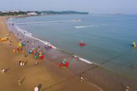 6月24日,游客在浙江省舟山市朱家尖南沙景區的沙灘上游玩(無人機照片)。