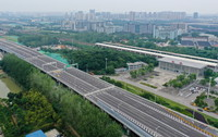 6月30日,車輛行駛在312國道南京段改擴建工程主線高架橋上(無人機照片)。