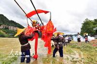 7月4日,貴州省臺江縣施洞鎮清水江,參加獨木龍舟競渡的苗族村民在龍舟上系上親戚們送的紅綢。