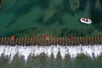 """7月6日,杭州市臨安區湍口鎮迎豐村的""""河小二""""黨員志愿者對塘溪進行日常河道保潔及巡查(無人機照片)。"""