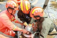 7月30日,河南省卫辉市健康路卫河河畔,消防员正在清理排涝泵。