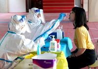 8月2日,在郑州市金水区的一个核酸检测点,医务人员对市民进行核酸检测取样。新华社记者 李安 摄