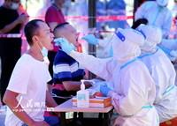 2021-10-27,在广东省鹤山市鹤山广场,医务人员对市民进行核酸检测取样。