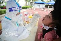 8月5日,在江苏省扬州市育才小学核酸检测点,医务人员为小朋友进行核酸检测采样。