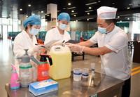 8月9日,在北京交通大学学生第二食堂,校医院医护人员(左、中)指导食堂工作人员进行消毒工作。