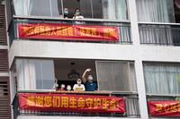 8月10日,在张家界市月亮湾花园小区,居家隔离的群众向在对面酒店居住的医务人员致意。