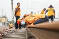 2021-10-27,郑州桥工段工作人员俯身查看陇海线设备平顺状态。