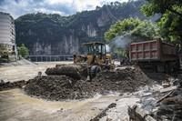8月30日,在重庆市巫溪县宁河街道漫滩路,工作人员清理洪水退去后留下的泥沙。
