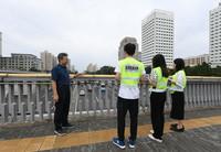 在北京西直门桥,邵春福(左一)在数车前与学生们交流(8月28日摄)。
