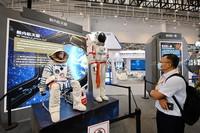 """9月8日,参观者在展览上观看展出的""""舱内航天服""""。"""