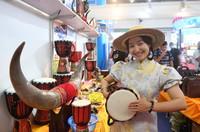 9月12日,在广西南宁国际会展中心,一名女子敲起加纳展台的鼓。新华社记者 陆波岸 摄