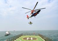 9月13日,在河北曹妃甸海域,救助直升机救生员模拟转移获救落水人员。