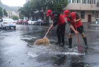 9月14日,舟山朱家尖街道办事处的党员志愿者在清理路面积水。