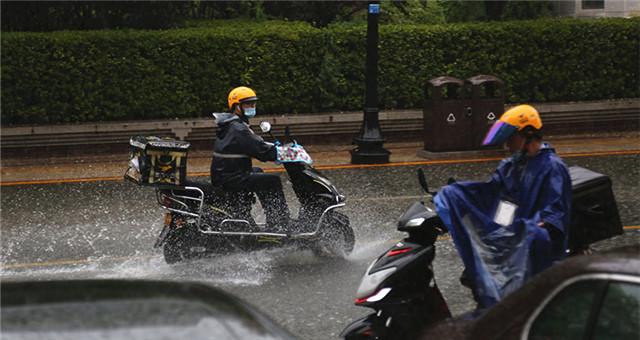 天津降雨升级 外卖小哥破浪前行